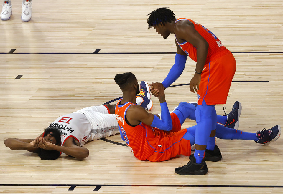 Photo - Oklahoma City Thunder's Nerlens Noel is helped up by teammate Luguentz Dort after falling with Houston Rockets' James Harden during the second quarter in Game 3 of an NBA basketball first-round playoff series, Saturday, Aug. 22, 2020, in Lake Buena Vista, Fla. (Mike Ehrmann/Pool Photo via AP)