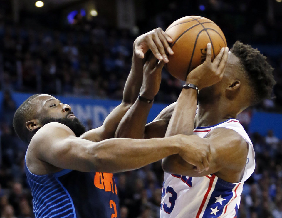 Photo - Oklahoma City's Raymond Felton (2) fouls Philadelphia's Jimmy Butler (23) in the third quarter during an NBA basketball game between the Philadelphia 76ers and the Oklahoma City Thunder at Chesapeake Energy Arena in Oklahoma City, Thursday, Feb. 28, 2019. Philadelphia won 108-104. Photo by Nate Billings, The Oklahoman