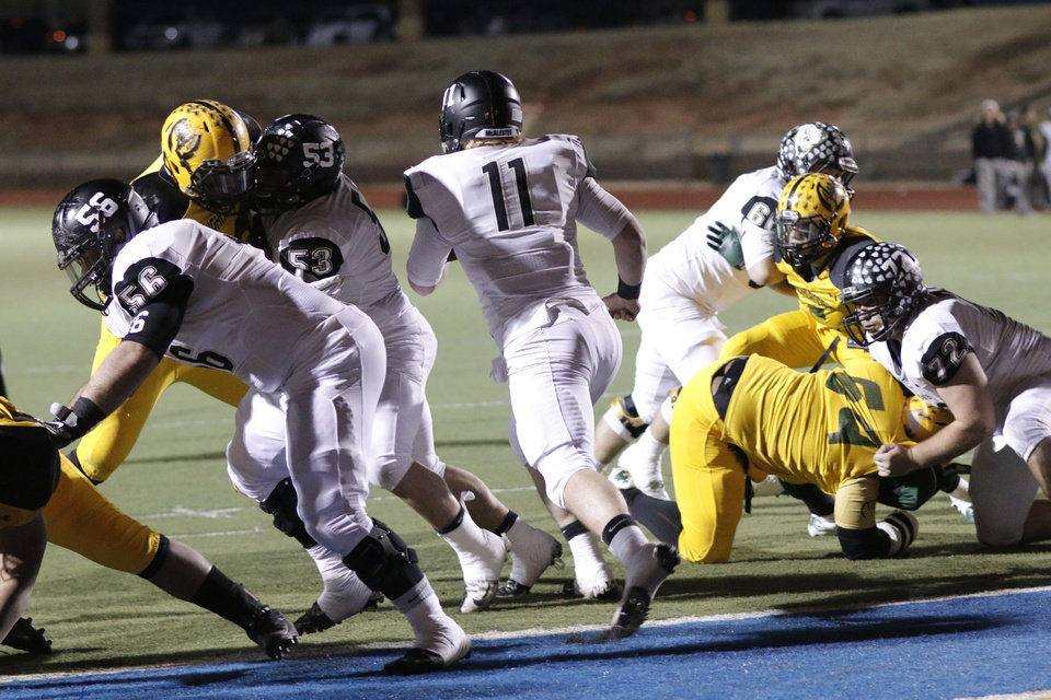 Photo - MHS #11 Dalton Wood hits a hole on a QB keeper that went for 99 years and a touchdown during the high school football playoff between McAlester and Lawton MacArthur at Choctaw stadium, November 28, 2014. Photo by Doug Hoke, The Oklahoman