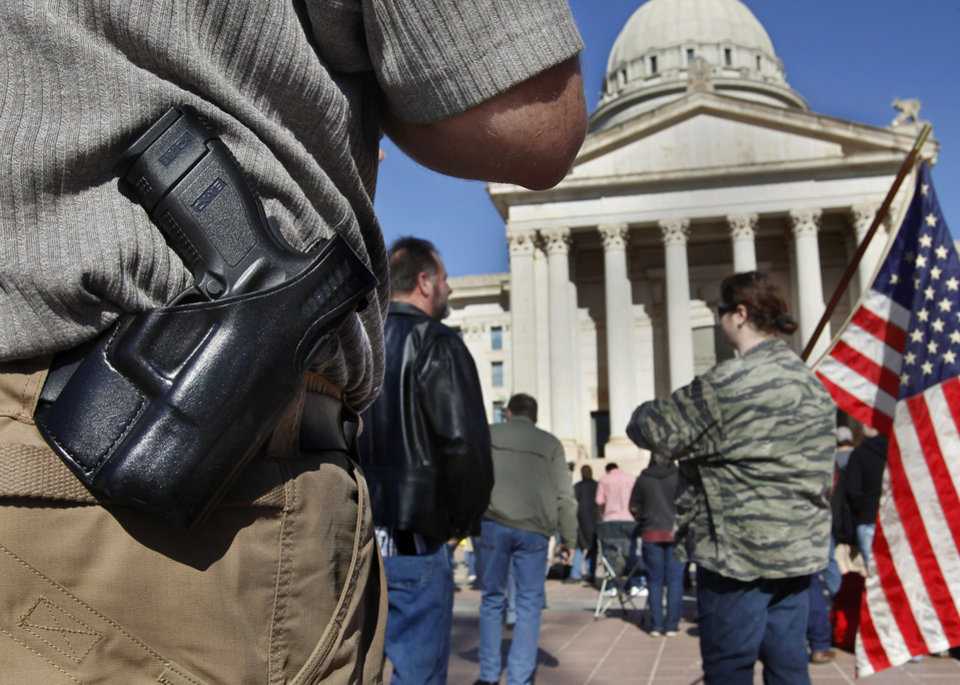 Photo - David Bradley of Moore, Okla., wears a pistol on his belt at the rally. He applied for his permit about two years ago. Organizers said an estimated 1800 people from throughout Oklahoma crowded into the south plaza at the state Capitol Saturday afternoon, Jan. 19, 2013, to voice their support for their second amendment rights and to express  concerns about proposed gun control legislation being considered by the federal government in the wake of the school shooting in Connecticut last month. Many  held aloft hand-made signs or waved American flags as speakers addressed the gun rights rally. Oklahoma passed an open carry law that recently took effect allowing citizens to openly carry a holstered weapon on their body if they have been granted a license.  Photo by Jim Beckel, The Oklahoman