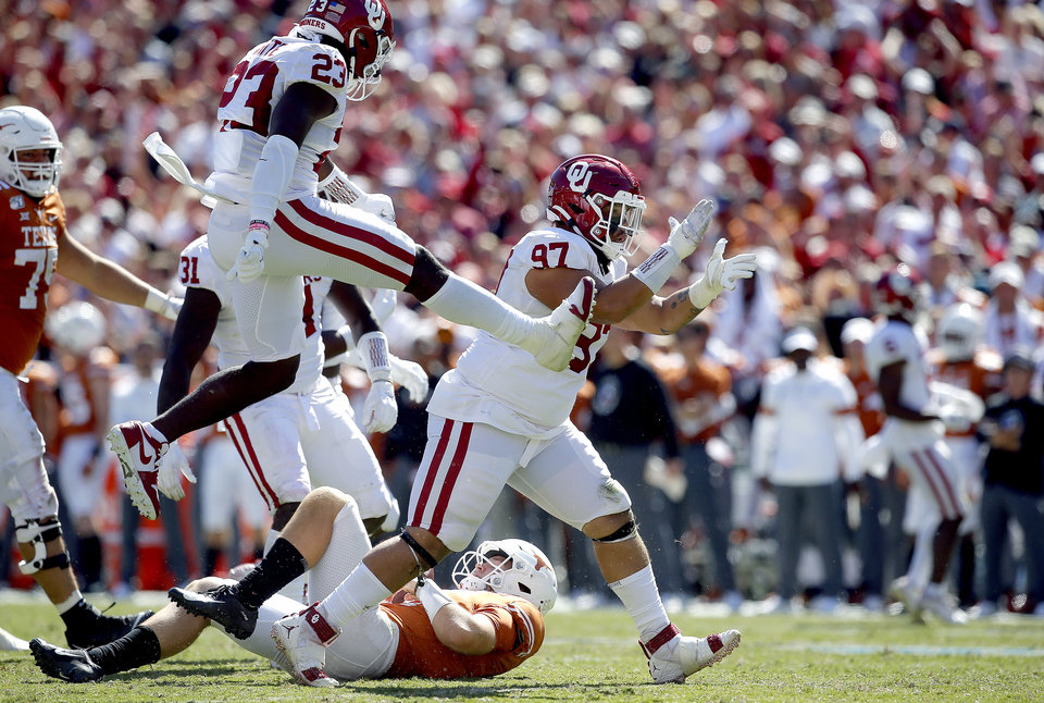 Photo - Oklahoma's Marquise Overton (97) celebrates his sack on Texas quarterback Sam Ehlinger (11) in the fourth quarter with Reed Lindsey (93) during the Red River Showdown college football game between the University of Oklahoma Sooners (OU) and the Texas Longhorns (UT) at Cotton Bowl Stadium in Dallas, Saturday, Oct. 12, 2019. OU won 34-27. [Sarah Phipps/The Oklahoman]