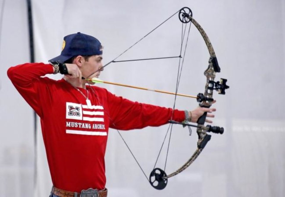 Photo -  Caden Owens, a junior at Mustang High School, shoots in the varsity archery competition Wednesday during the Western Tier 2 state shoot at OKC State Fair Park. [SARAH PHIPPS/THE OKLAHOMAN]