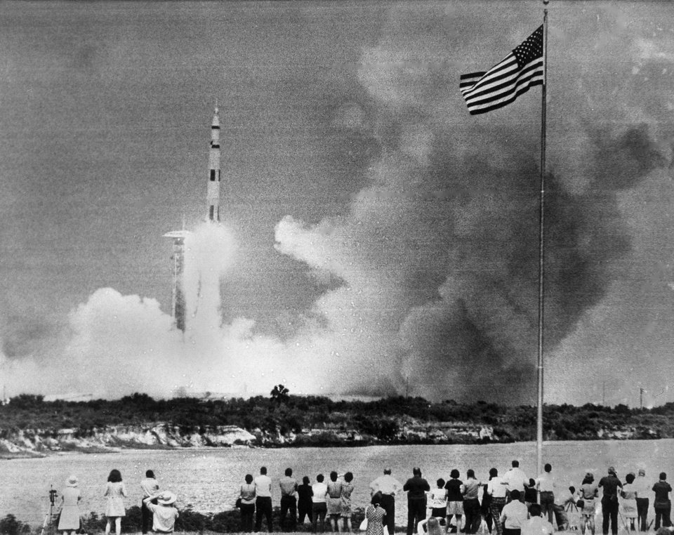 Photo -  FILE - In this April 11, 1970 file photo, crowds watch the lift-off of the Saturn V rocket carrying the Apollo 13 spacecraft on its mission to the moon from Cape Kennedy, Fla. (AP Photo)