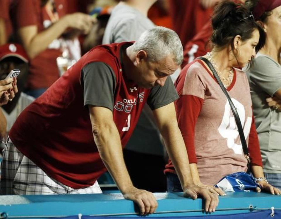Photo - Sooner fans' dejection set in during the fourth quarter of Oklahoma's 37-17 loss to Clemson Thursday in the Orange Bowl. [Photo by Nate Billings, The Oklahoman]