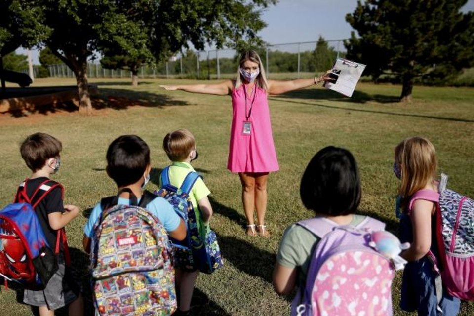 Photo -  Kindergarten teacher Lindsay Giddens holds her arms out to demonstrate to her students how to stayed spaced as they arrive for their first day of school at Edmond Public Schools' Charles Haskell Elementary. Edmond Public Schools opted for a blended learning model which has students alternate between at-home learning and attending class in person. [Bryan Terry/The Oklahoman]