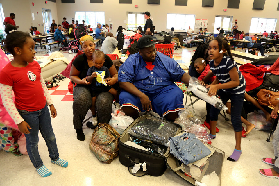 Photo - Family members, from left, Briana Jeunice, 7, Vernea Jones, 30, Greg Jones III, 18-motnhs Greg Jones Sr., 36, and Zahava Alexander, 7, settle into the Red Cross shelter at the Samuel S. Gaines Academy building in Fort Pierce Fla., Thursday Oct. 6, 2016, as Hurricane Matthew approaches Florida's east coast  (Douglas R. Clifford/Tampa Bay Times via AP)