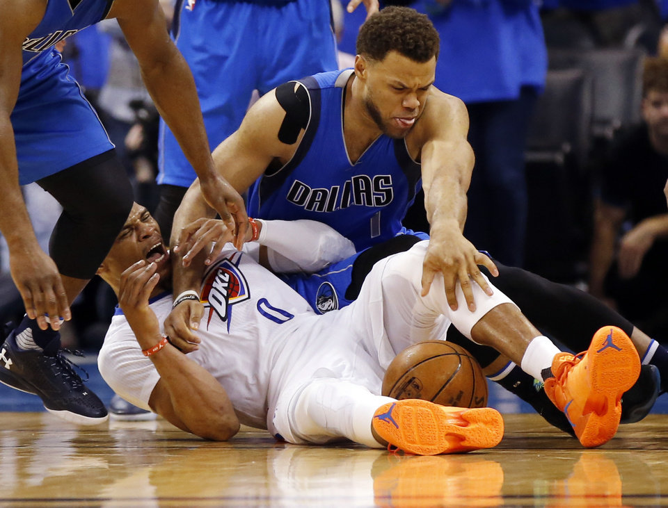 Photo - Oklahoma City's Russell Westbrook (0) and Dallas' Justin Anderson (1) battle for the ball late in the fourth quarter during Game 5 of the first round series between the Oklahoma City Thunder and the Dallas Mavericks in the NBA playoffs at Chesapeake Energy Arena in Oklahoma City, Monday, April 25, 2016. The play ended in a jump ball and a technical foul for Anderson. The Thunder won 118-104. Photo by Nate Billings, The Oklahoman