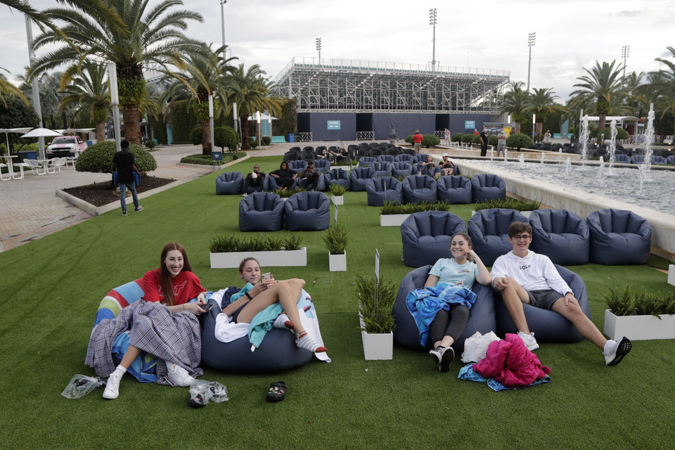 Photo -  People sit outdoors to watch a movie as part of a program offered by the Miami Dolphins on June 18, at Hard Rock Stadium during the coronavirus pandemic in Miami Gardens, Fla. [Lynne Sladky/The Associated Press]