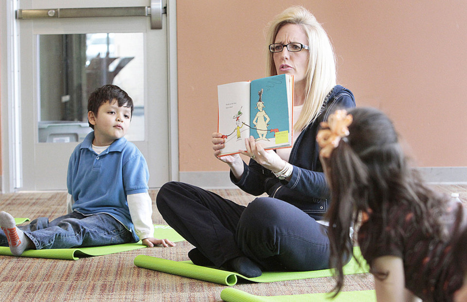 Photo - Angela Moorad uses Dr. Seuss characters to illustrate poses as she teaches yoga to 3- and 4-year-olds on Wednesday.