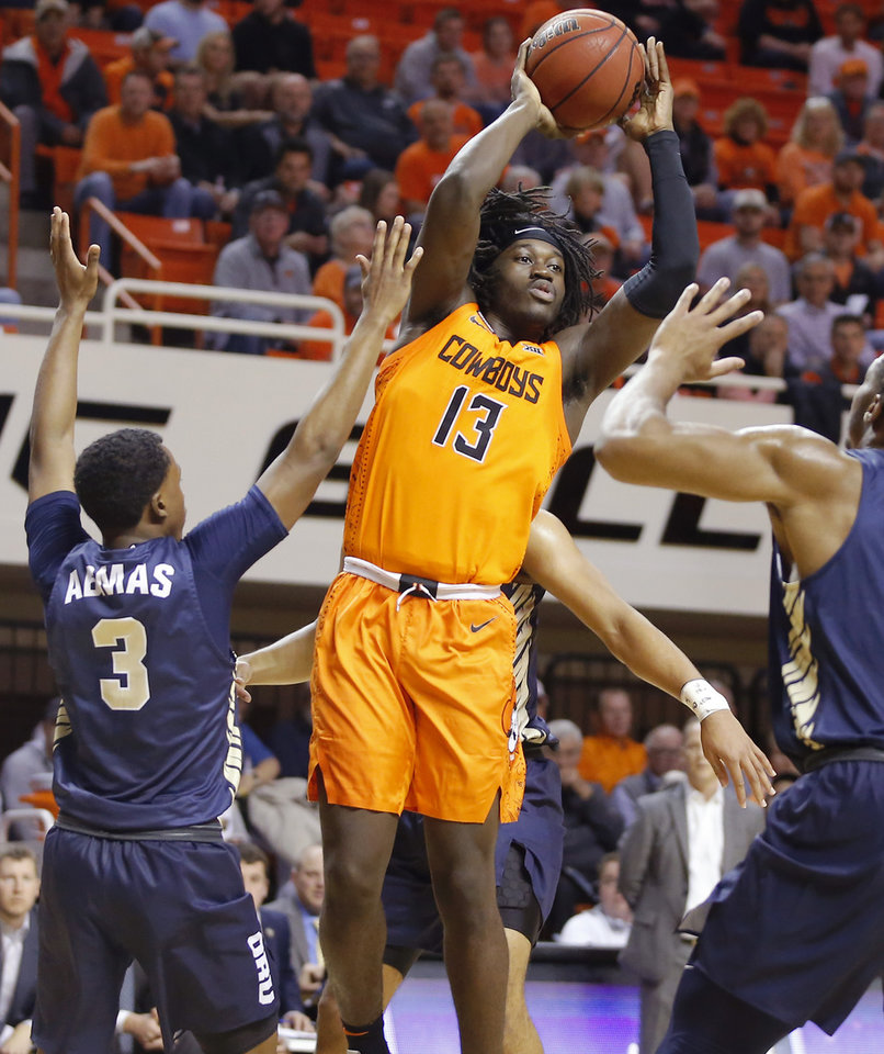 Photo - Oklahoma State's Isaac Likekele (13) passes the ball as Oral Roberts's Max Abmas (3) defends during an NCAA basketball game between the Oklahoma State University Cowboys (OSU) and the Oral Roberts Golden Eagles (ORU) at Gallagher-Iba Arena in Stillwater, Okla., Wednesday, Nov. 6, 2019. [Bryan Terry/The Oklahoman]