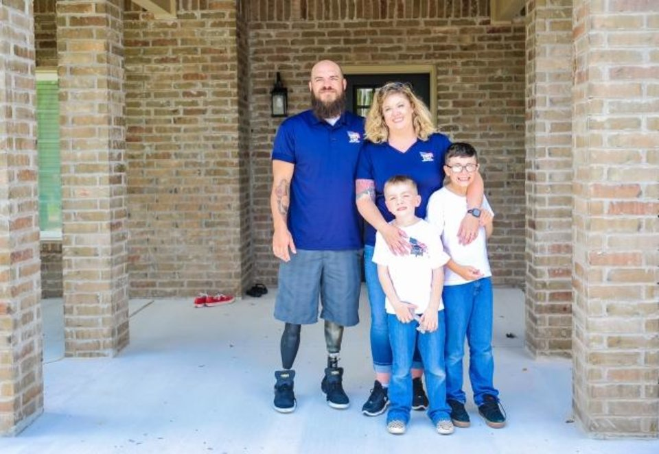 Photo -  U.S. Army Spc. Adam Putt, his wife, Tiffany, and sons Victor and Virgil, are shown at their new Blanchard home, donated by Homes For Our Troops. [HFOT]