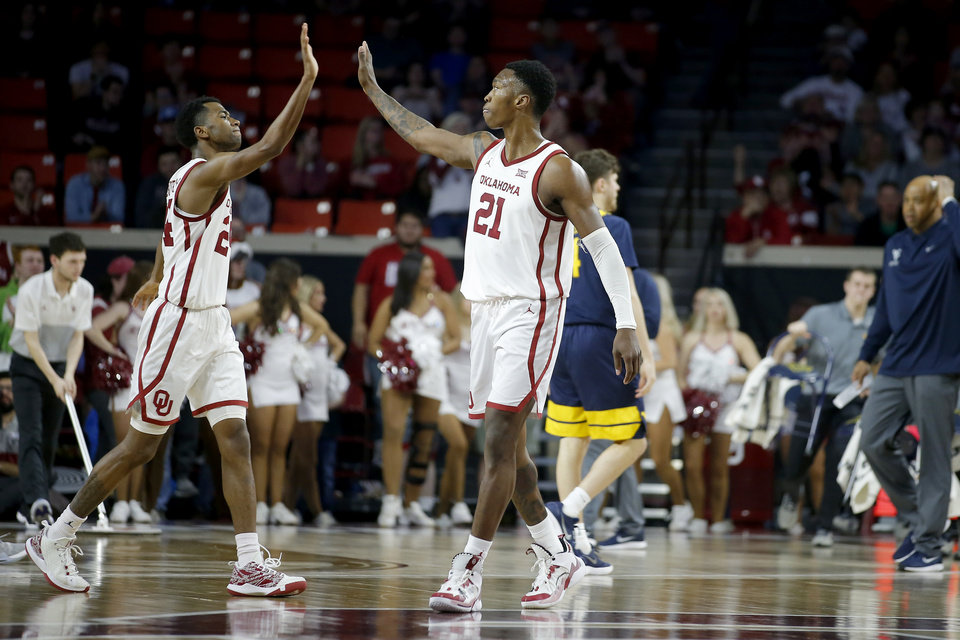 Photo - Oklahoma's Jamal Bieniemy (24) and Kristian Doolittle (21) high-five during an NCAA mens college basketball game between the University of Oklahoma Sooners (OU) and the West Virginia Mountaineers at the Lloyd Noble Center in Norman, Okla.,Saturday, Feb. 8, 2020. Oklahoma won 69-59. [Bryan Terry/The Oklahoman]