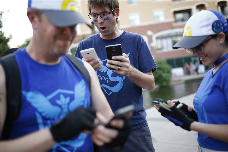 Photo - Clint Buckley of Edmond plays Pokemon Go with John and Carissa Eads of Mustang along the Bricktown Canal during a meetup for players of the game in Oklahoma City at Bricktown on Friday, July 29, 2016. Photo by Bryan Terry, The Oklahoman