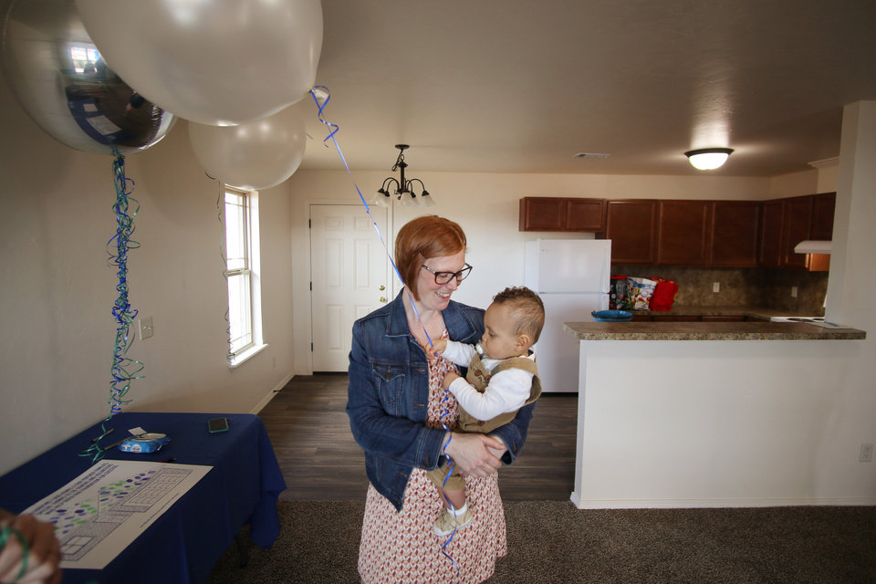 Photo - Brittani Githiri holds her one year old son, Piaget, as she looks around the finished house for the first time. Habitat for Humanity's 1,000th home, Monday, March 9, 2020.  [Photo by Doug Hoke/The Oklahoman]