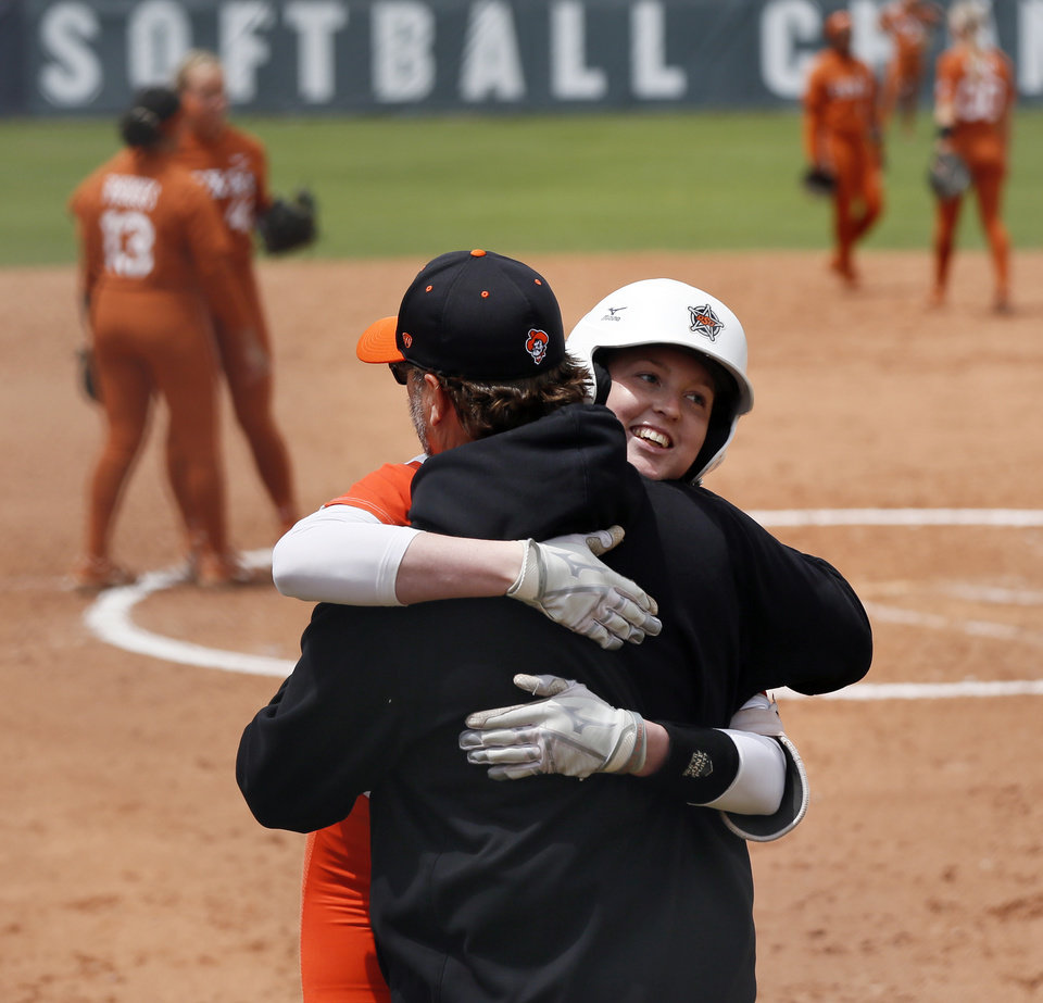 Photo - OSU's Sydney Springfield (15) hugs head coach Kenny Gajewski as she leaves the game for a pinch runner after hitting a two-RBI single in the sixth inning during a game between Oklahoma State and Texas in the Big 12 softball tournament at  in Oklahoma City, Friday, May 10, 2019. OSU beat UT 6-2. [Nate Billings/The Oklahoman]