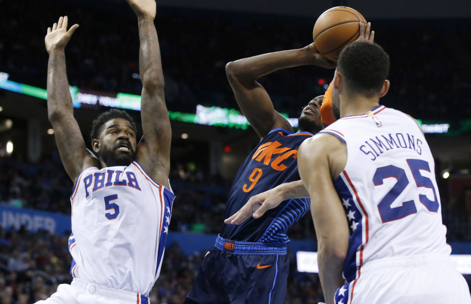 Photo - Oklahoma City Thunder forward Jerami Grant (9) shoots between Philadelphia 76ers center Amir Johnson (5) and guard Ben Simmons (25) during the second half of an NBA basketball game Thursday, Feb. 28, 2019, in Oklahoma City. (AP Photo/Sue Ogrocki)