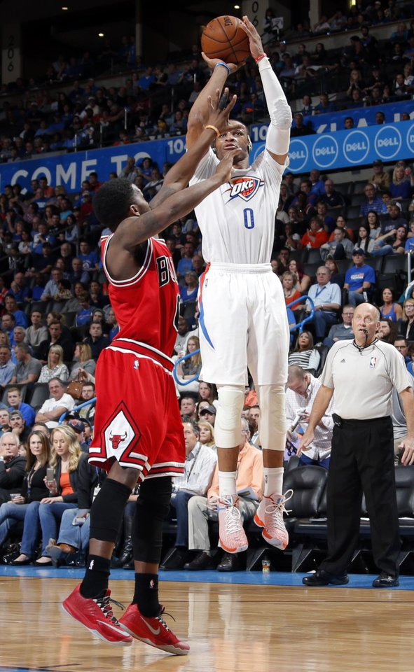 Photo - Russell Westbrook (0) shoos over Chicago's Aaron Brooks (0) during the NBA game between the Oklahoma City Thunder and the Chicago Bulls at Chesapeake Energy Arena in Oklahoma City, Sunday, March  15, 2015. Photo by Sarah Phipps, The Oklahoman