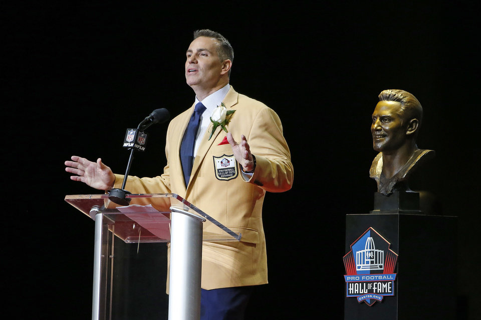 Former NFL quarterback Kurt Warner speaks next to a bust of him during  inductions at the 46c304851