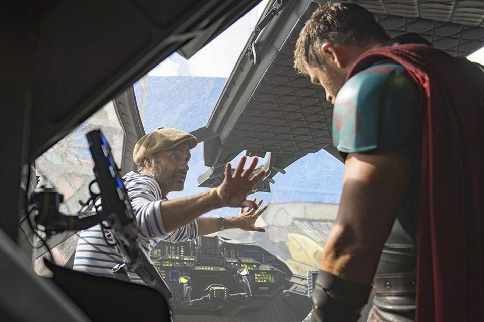 Photo - Director Taika Waititi, left, works with actor Chris Hemsworth on the set of