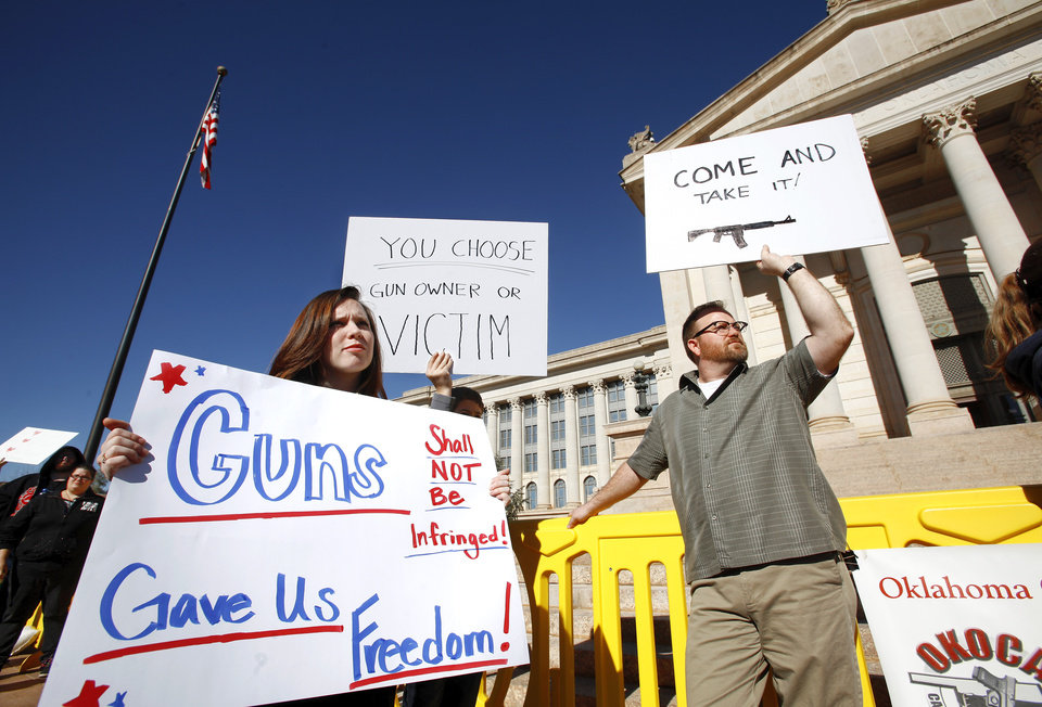 Photo - Robyn Sheridan, left, and Adam Cox, both of Edmond display their signs at the rally. Middle sign is held by Cox's son, Aaron.  Organizers said an estimated 1800 people from throughout Oklahoma crowded into the south plaza at the state Capitol Saturday afternoon, Jan. 19, 2013, to voice their support for their second amendment rights and to express  concerns about proposed gun control legislation being considered by the federal government in the wake of the school shooting in Connecticut last month. Many  held aloft hand-made signs or waved American flags as speakers addressed the gun rights rally.  Photo by Jim Beckel, The Oklahoman