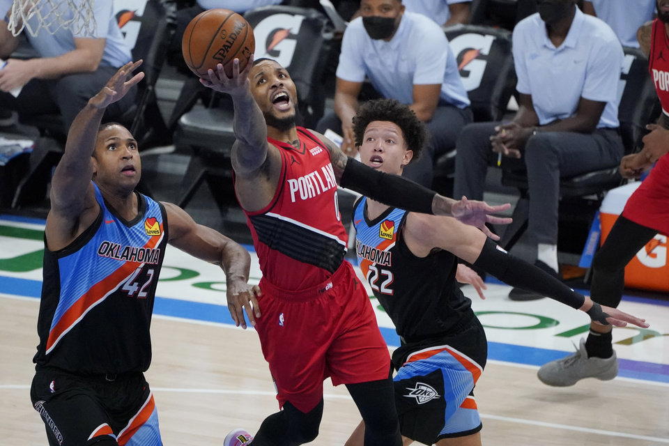 Photo - Portland Trail Blazers guard Damian Lillard (0) shoots between Oklahoma City Thunder center Al Horford (42) and center Isaiah Roby (22) in the second half of an NBA basketball game Tuesday, Feb. 16, 2021, in Oklahoma City. (AP Photo/Sue Ogrocki)