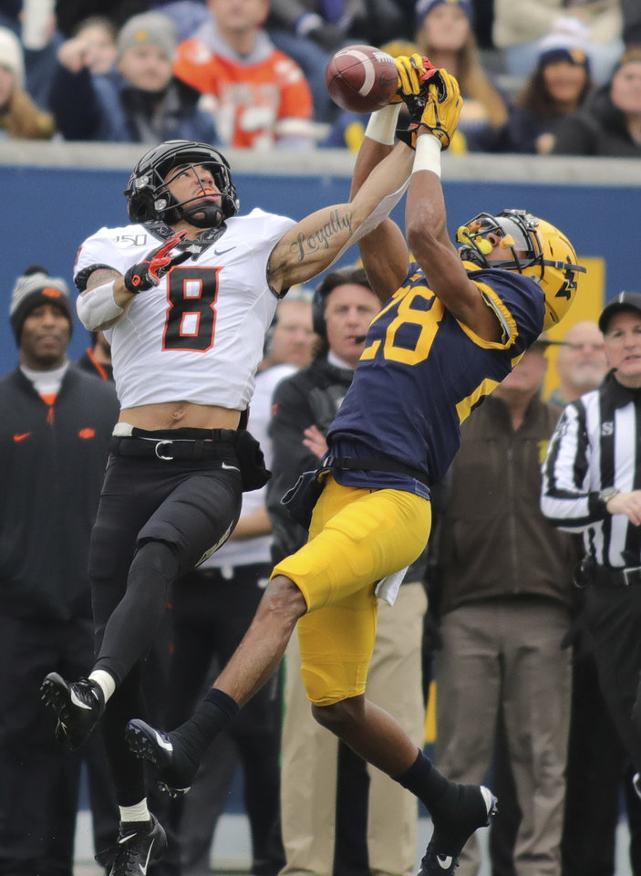 Photo - West Virginia's Keith Washington (28) breaks up a pass intended for Oklahoma State's Brayden Johnson (8) during their NCAA college football game  in Morgantown, W.Va., on Saturday, Nov. 23, 2019. [AP Photo/Chris Jackson]
