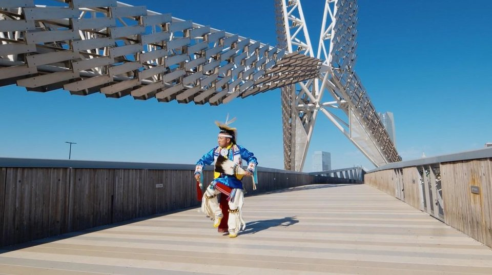 Photo - Sgt. Denny MedicineBird, a Cheyenne Arapaho and Kiow dancer from Jones, dances across the Skydance Bridge as part of the