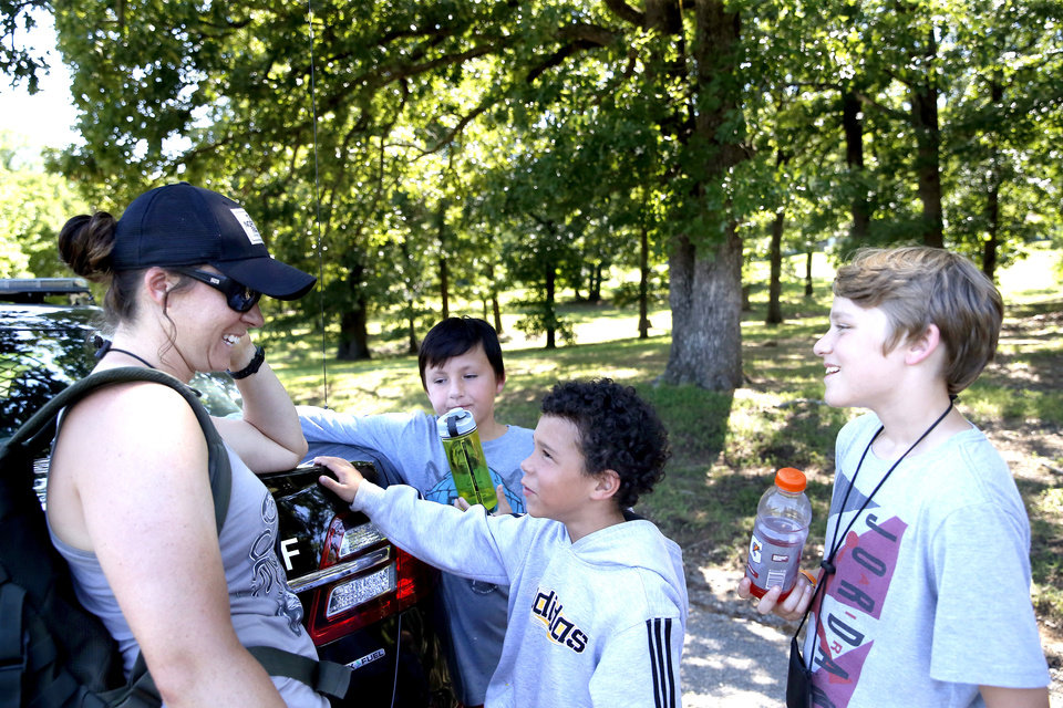 Photo -  Sgt. Liz Herman talks with youths June 21 during Camp Hope in Chouteau. The camp is for children who have experienced trauma. [Photo by Sarah Phipps, The Oklahoman]