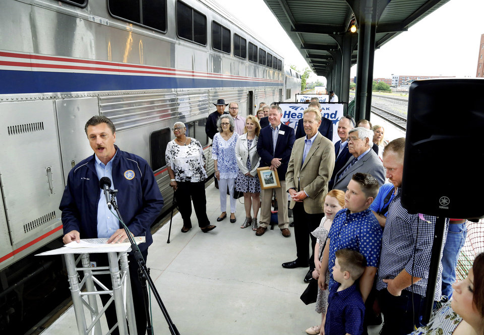 Photo - Standing beside an Amtrak passenger car just a few minutes before it pulls away from the station, Tim Gatz, Oklahoma secretary of transportation, welcomes dignitaries and visitors to the ceremony marking the 20th anniversary of the return of passenger rail service to Oklahoma at Santa Fe Depot in downtown Oklahoma City Friday morning, June 14, 2019. The Heartland Flyer is celebrating its 20th year of serving passengers in Oklahoma and Texas.   The Heartland Flyer, which runs daily, has carried more than 1.4 million passengers between Oklahoma City and Fort Worth during the past two decades. Originating its route on Oklahoma City, the Heartland Flyer connects to the Texas Eagle train in Fort Worth, which provides service to major cities including Dallas, Little Rock, St. Louis or Austin and San Antonio. Gatz also serves as the executive director of the Oklahoma Department of Transportation. [Jim Beckel/The Oklahoman]