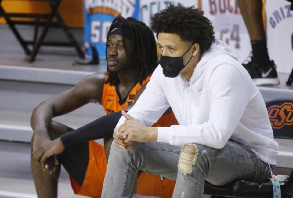 Photo -  Cade Cunningham, right, and Isaac Likekele watch the finals minutes of Baylor's 81-66 win at Oklahoma State on Saturday. [Bryan Terry/The Oklahoman]