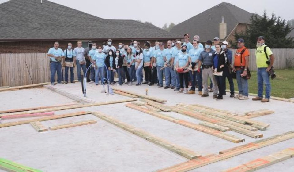 Photo -  Oklahoma City Police Department officers and employees pose with metro church members before building a Habitat for Humanity home on Friday as part of