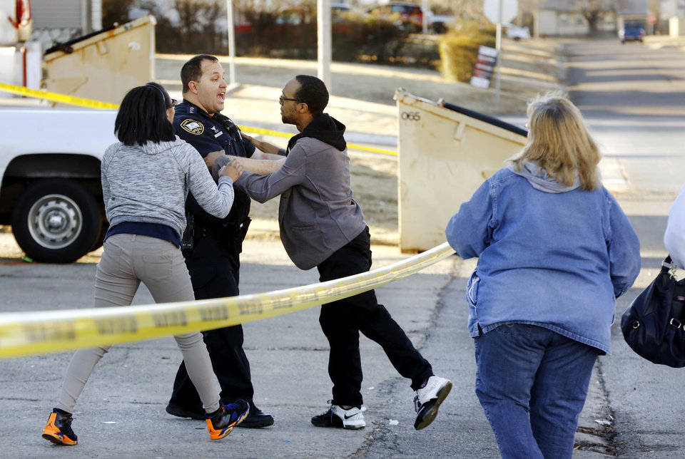 Photo -  A police officer stops a man as he runs through police tape at Laundry Station, 4000 SE 15, before being restrained by officers. He said he was the son of the woman inside. [Photo by Jim Beckel, The Oklahoman]
