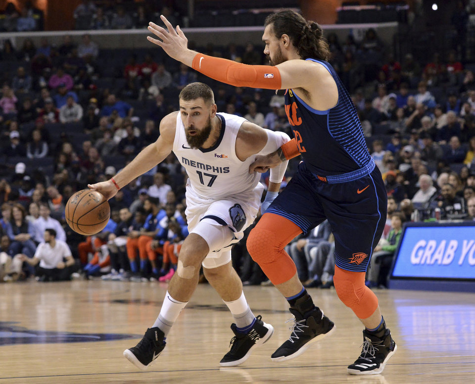 Photo - Memphis Grizzlies center Jonas Valanciunas (17) drives against Oklahoma City Thunder center Steven Adams (12) during the first half of an NBA basketball game Monday, March 25, 2019, in Memphis, Tenn. (AP Photo/Brandon Dill)