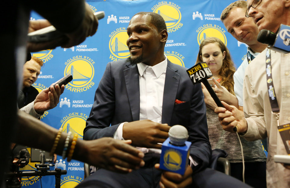 Photo - Golden State Warriors' Kevin Durant speaks with reporters after he was introduced during a news conference at the NBA basketball team's practice facility, Thursday, July 7, 2016, in Oakland, Calif. (AP Photo/Beck Diefenbach)