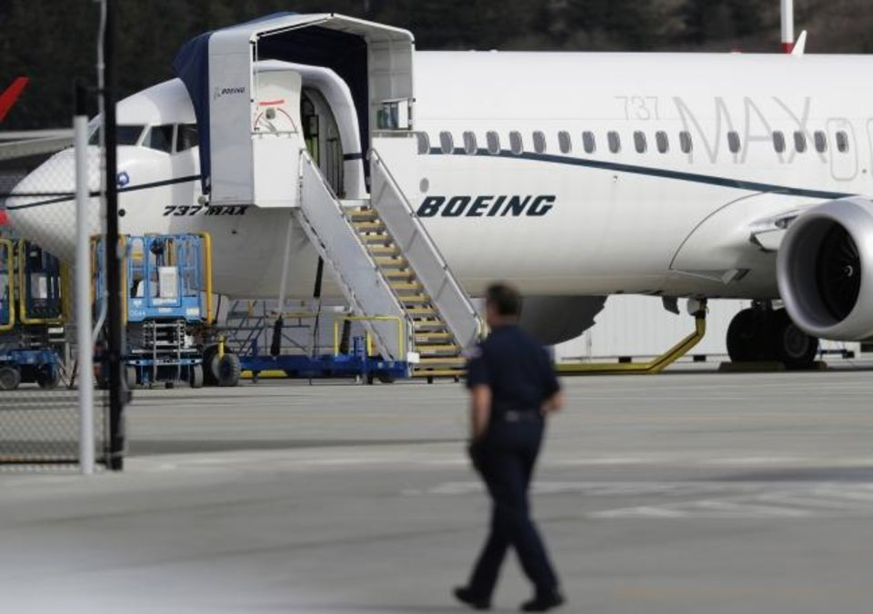 Photo -  A worker walks next to a Boeing 737 MAX 8 airplane parked at Boeing Field in Seattle. [AP PHOTO]