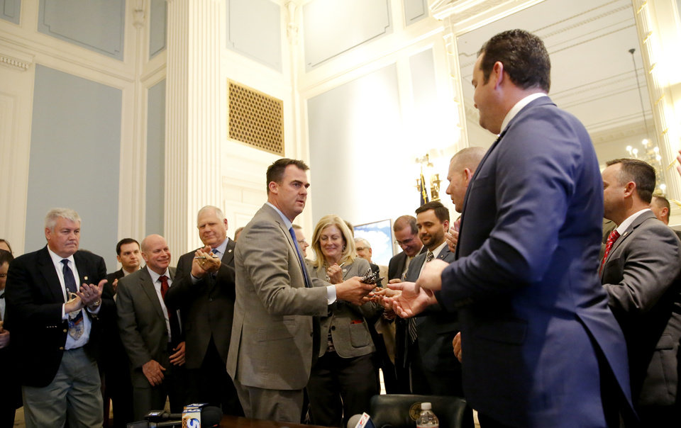 Photo - Oklahoma Gov. Kevin Stitt hands out pens after signing the HB 2597 at the Blue Room at the state Capitol in Oklahoma City,  Wednesday, Feb. 27, 2019. Photo by Sarah Phipps, The Oklahoman