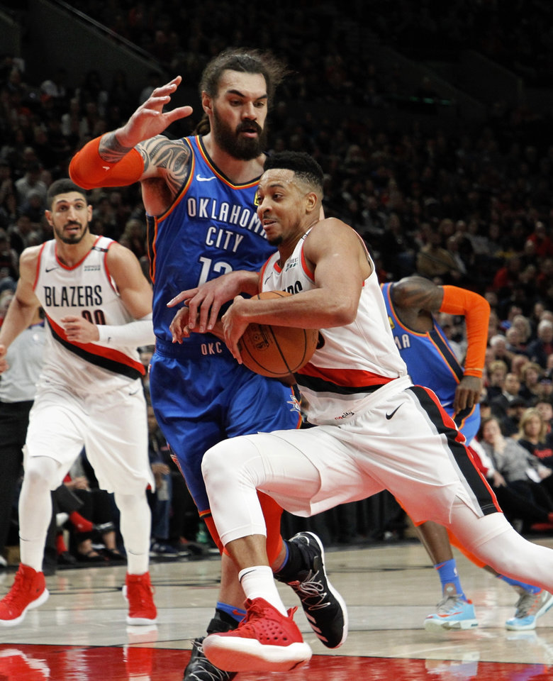 Photo - Portland Trail Blazers guard CJ McCollum, right, drives against Oklahoma City Thunder center Steven Adams, front left, during the second half of Game 1 of a first-round NBA basketball playoff series in Portland, Ore., Sunday, April 14, 2019. (AP Photo/Steve Dipaola)