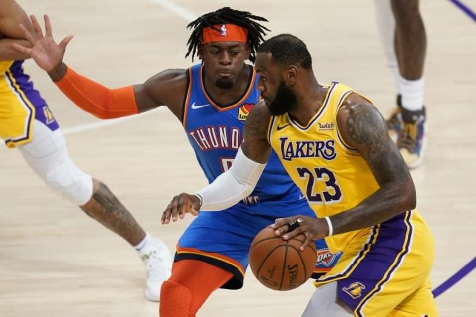 Photo -  Thunder guard Luguentz Dort defends Lakers forward LeBron James (23) during the second quarter of Wednesday's game in Los Angeles. [AP Photo/Ashley Landis]