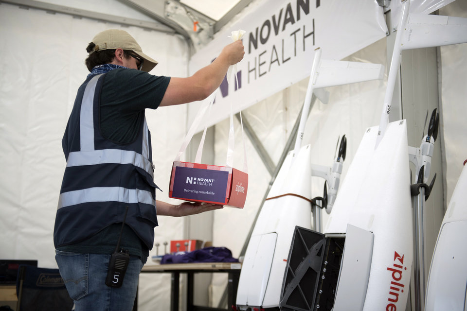 Photo -  A package is prepared to be placed inside a drone for delivery from Novant Health Logistics Center in Kannapolis, N.C., to Novant Health Medical Center in Huntersville, N.C. [Davis Turner/Novant Health via The Associated Press]