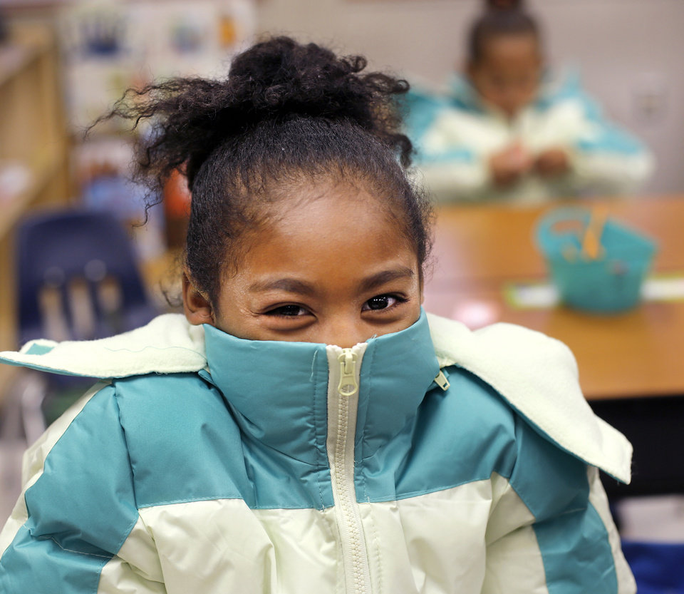 Photo - Rhianna Wheeler slips into her new winter jacket  in Morgan Riklin's kindergarten classroom at Shidler Elementary School, located on S. Byers, just south of downtown.  Nearly 400 students in need received new coats on Wednesday, Oct. 5, 2016, courtesy of a joint effort by Love's Travel Stops and The Foundation for Oklahoma City Public Schools.  Love's is funding $120,000 worth of projects in the Oklahoma City school district projects and and initiatives through the foundation. Included in that amount is $70,000 for the Coat-a-Kid program, which provides new winter coats. Photo by Jim Beckel, The Oklahoman