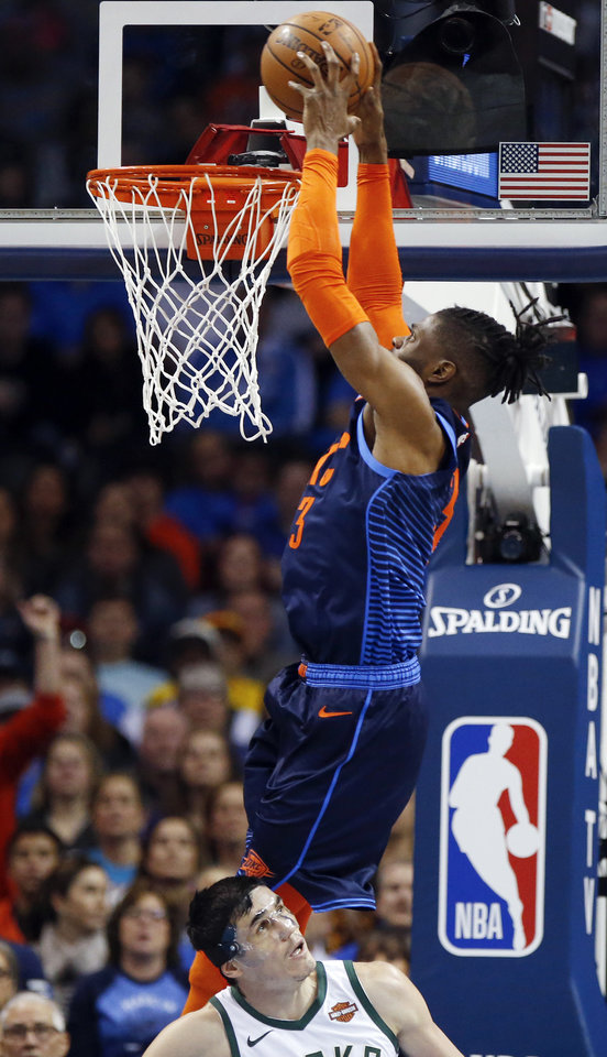 Photo - Oklahoma City's Nerlens Noel (3) dunks the ball over Milwaukee's Ersan Ilyasova (77) during an NBA basketball game between the Milwaukee Bucks and the Oklahoma City Thunder at Chesapeake Energy Arena in Oklahoma City, Sunday, Jan. 27, 2019. Photo by Nate Billings, The Oklahoman