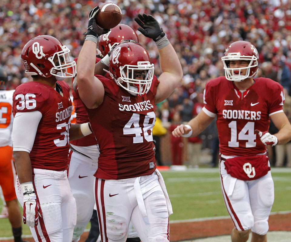 Photo - Oklahoma's Aaron Ripkowski (48) celebrates a touchdown during a Bedlam college football game between the University of Oklahoma Sooners (OU) and the Oklahoma State University Cowboys (OSU) at the Gaylord Family Oklahoma Memorial Stadium in Norman, Okla. on Saturday, Dec. 6, 2014. Photo by Chris Landsberger, The Oklahoman