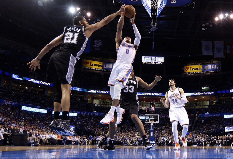 Photo - Oklahoma City's Russell Westbrook (0) goes to the basket as San Antonio's Tim Duncan (21) defends during a NBA game between the Oklahoma City Thunder and the San Antonio Spurs at the Chesapeake Energy Arena, Tuesday, April 7, 2015, in Oklahoma City. Photo by Sarah Phipps, The Oklahoman