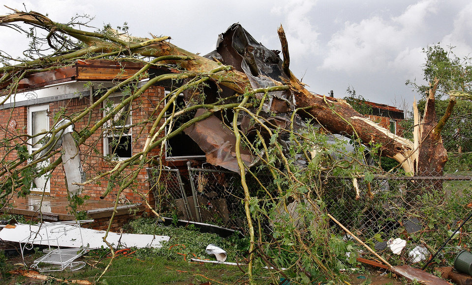 Photo - A large tree rests on top of this brick home on SH 74F near Cashion after a tornado raced across Logan County  Tuesday afternoon,  May 24, 2011,   The home's roof was pulled away and more than a dozen trees on the property were knocked down. Photo by Jim Beckel, The Oklahoman
