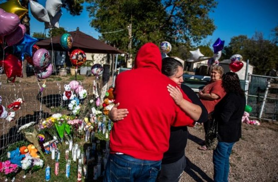 Photo -  Arnold Erazo and Maria Varela share an emotional embrace on Thursday at a makeshift memorial for three children, 3-year-old Zane Ezri Henry, 23-month-old Mireya Henry and 6-month-old Catalaya Kyeana Rios, who police say were killed by their mother in Phoenix. Erazo and Varela, who both have children, said they couldn't imagine losing them. [Arizona Republic]