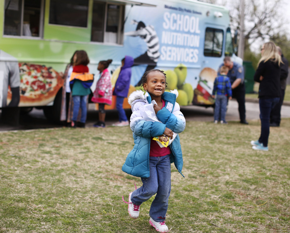 Photo -  Students receive sack lunches from a food truck provided by Oklahoma City Public Schools Nutrition Services on Monday. As a result of the teacher walkout, children who spent their day at the Boys and Girls Club of Oklahoma County received free lunches from the school district. [Photo by Jim Beckel, The Oklahoman]