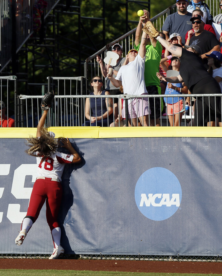 Photo - Fans try to catch a home-run ball by UCLA's Aaliyah Jordan (23), not pictured, over OU's Jocelyn Alo (78) in the first inning during the first NCAA softball game in the championship series of the Women's College World Series between Oklahoma and UCLA at USA Softball Hall of Fame Stadium in Oklahoma City, Monday, June 3, 2019. [Nate Billings/The Oklahoman]
