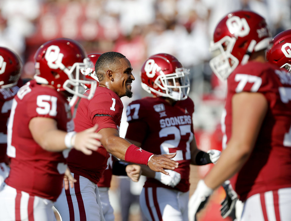 Photo - Oklahoma's Jalen Hurts (1) high fives team mates during a college football game between the University of Oklahoma Sooners (OU) and the Houston Cougars at Gaylord Family-Oklahoma Memorial Stadium in Norman, Okla., Sunday, Sept. 1, 2019. [Sarah Phipps/The Oklahoman]