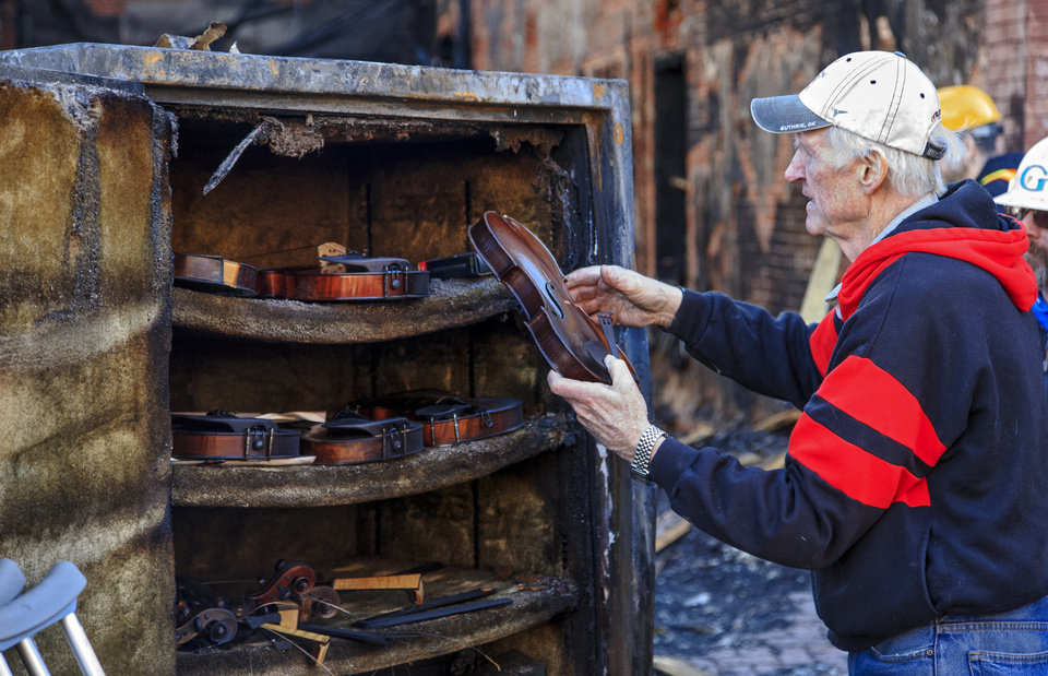 Photo - Fiddle player Byron Berline looks over the damage on violins recovered from a safe that was part of the items destroyed by a fire at his fiddle shop in Guthrie, Okla. on Monday, Feb. 25, 2019. The fire on Saturday destroyed two businesses in historic downtown Guthrie.   Photo by Chris Landsberger, The Oklahoman