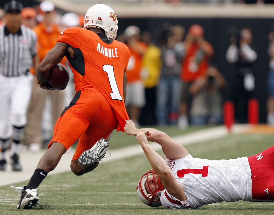 Photo - OSU's Joseph Randle slips past Nebraska's Adi Kunatic during the college football game between the Oklahoma State Cowboys (OSU) and the Nebraska Huskers (NU) at Boone Pickens Stadium in Stillwater, Okla., Saturday, Oct. 23, 2010. Photo by Sarah Phipps, The Oklahoman
